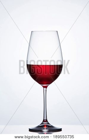 Elegant crystal wine glass with red wine against light background with reflection. Clarity wineglass and wine. Luxury and relaxation. Viticulture, grapes and winery. Sommelier and tasting.