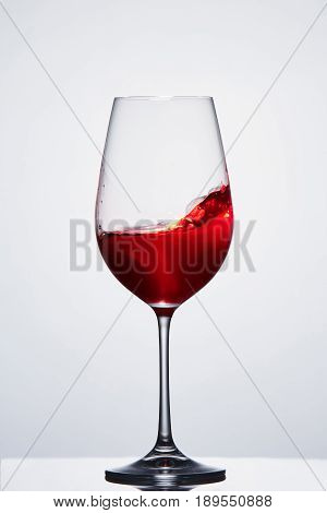 Red wine in a crystal pure wineglass showing waves against light background. Luxury lifestyle and relaxation. Motion in the wineglass. Sommelier and tasting.