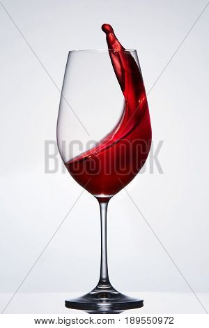 Red wine splashing from the pure elegant wineglass standing against light background with reflection. Moving in the wineglass. Sommelier and tasting. Viticulture, grapes and winery.