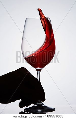 Hand holds a pure wineglass with splashing red wine standing aginst light background. Moving in the wineglass. Sommelier and tasting. Viticulture, grapes and winery. Luxury lifestyle.