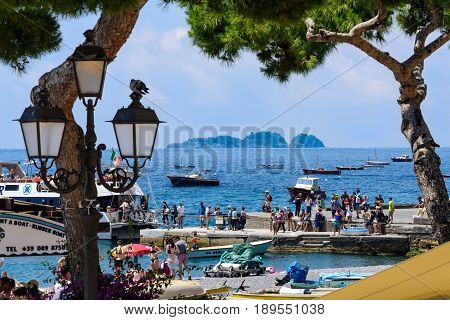 Positano Italy - June 11 2016: Tourists gather at a boat marina for boat tours along the Amalfi Coastline in Italy.