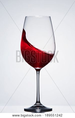 Splashing red wine with wave in the elegant wineglass standing against light background with reflection. Concept of the luxury lifestyle and relaxation. Still-life and background. Sommelier and tasting.