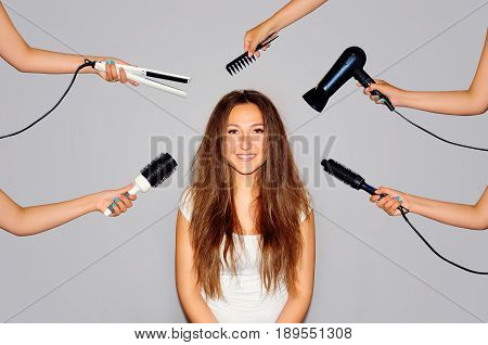 Health and beauty. Young woman getting a beauty and hair style in the same time with hands making different works. Styling of disobedient hair. Close-up portrait on gray background.
