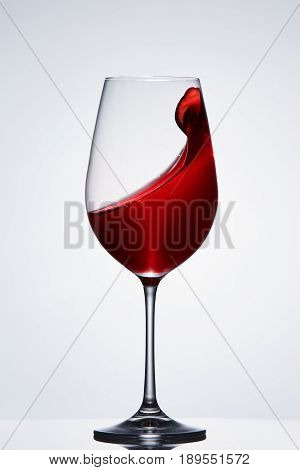 Wave of the romantic drink red wine on the pure wineglass standing against light background with reflection. Brightly wine and elegant goblen. Luxury lifestyle. Sommelier and tasting. Viticuclture, grapes and winery. Vertical photo.