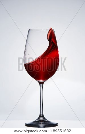Elegant pure wineglass with wave of brightly red wine standing against light background with reflection in down. Relaxation and luxury lifestyle. Tasty and natural drink. Sommelier and tasting. Vertical photo.