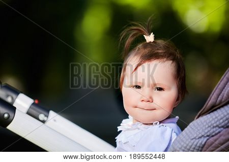 Portrait of the happy baby girl in a stroller in the city park at warm sunshiny day. Cute little girl in the white dress. Summer or spring season in outside. Horizontal photo. Concept of the happy babies.