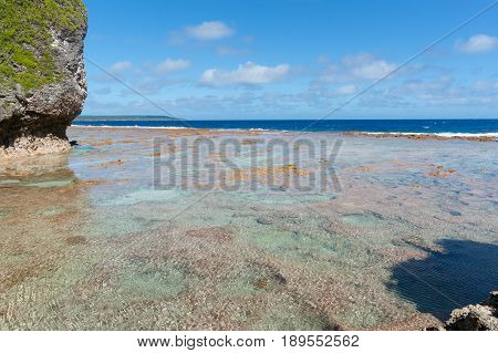 Three color areas of red colored mosaic-like pattern coral shelf with turquoise sea and blue sky beyond surounding bottom of tropical atoll island of Niue