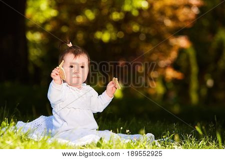 Portrait of happy joyful child sitting on the meadow and holds snack in the park. Cute baby girl in the white dress. Warm sunshiny day. Summer or spring season. Horizontal photo. Concept of the happy babies.