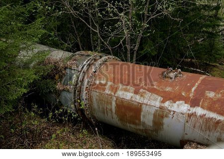 Rusty old turbine pipes in a spring forest