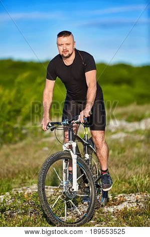 Portrait of athlete man riding mountain bike on the hill in summer season. Young cyclist in the black sportwear and with sportive shoes. Vertical photo. Beautiful landscape and blue sky like a background. Concept of the healthy lifestyle.