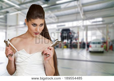Young Sexy Woman In A White Dress Holding A Wrenchs In Her Arms