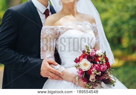 the bride and groom stand side by side and holding wedding bouquet