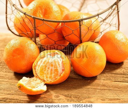 Group of tangerines in a basket with a peeled one in front