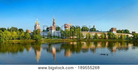 View on cloister monastery chapel walls, bell towers, pond with ducks. City park garden. Novodevichy Convent. Castle style monastery heritage legacy Famous tourist sightseeing holidays vacations tours