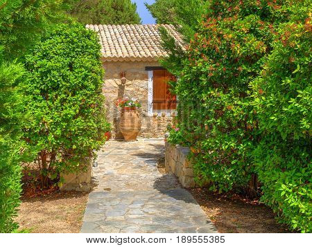 View on family Greece Greek village style hotel entrance, antique classical vase jar flowers. Greece holidays vacations sightseeing tours. Greece architecture