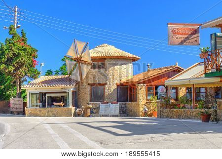 ZAKYNTHOS ISLAND, GREECE, JUNE 06, 2016: View on Windmill Taverna classical Greek restaurant with open BBQ grill and cooking pig and classical flouring-mill. Greece island holidays vacation. Greece