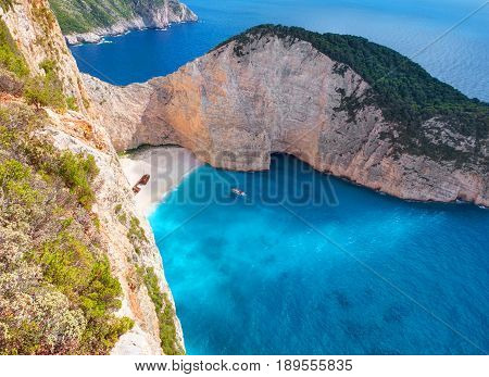 Beautiful view on shipwreck beach travel sightseeing boat swimming tourists in blue water of Ionian Sea near to Blue Caves and Navagio Beach view point. Greece Island Zakynthos Navagio shipwreck beach