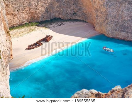 View on Shipwreck beach in amazing bay, boat ship with swimming people in Ionian Sea blue water Blue Caves. Greece islands Zakynthos Navagio beach sightseeing holidays vacations tours boat trip