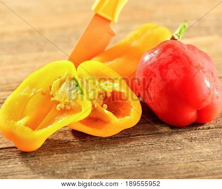Small bell peppers in different colors on a wooden base
