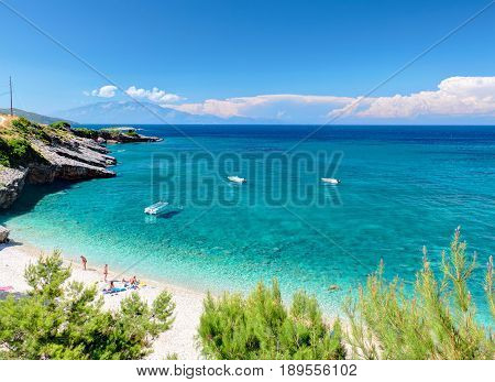 Beautiful view on Zakynthos stone and sand beach, stone rocks, swimming and toasting people on white sand beach, blue ultramarine water of Ionian Sea, reefs, white boats. Greece islands holidays tours