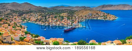 Panoramic view on beautiful Symi island Aegean Sea blue bay Greek houses on green hills, yacht sea port, tourist ferryboat. Famous Mediterranean MSC cruises. Greece islands holiday vacation tours trip