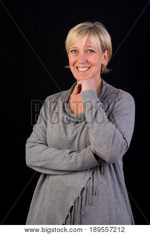 Beautiful european mature woman in gray dress, thoughtful, happy - photograph on black background