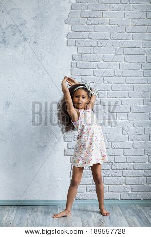 Cute Afro Girl Against The Gray Wall