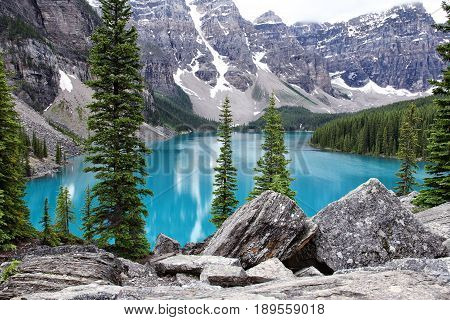 Lake Moraine Banff National Park Alberta Canada with beautiful blue water and snow-capped mountains with fog.