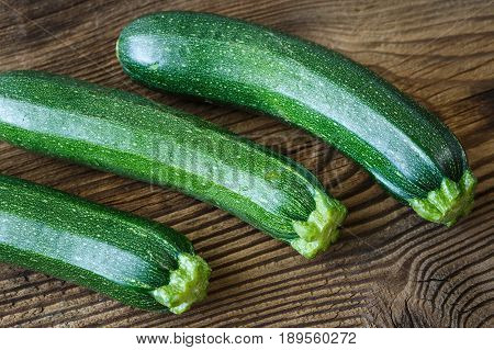 Fresh green zucchini on rustic wooden table
