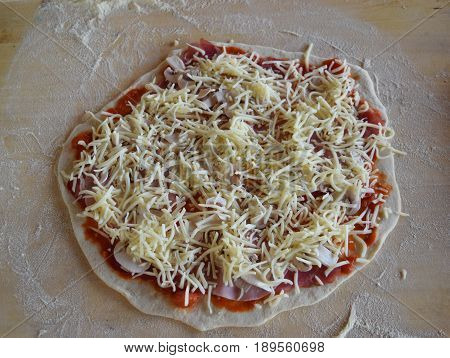 Cooking pizza, ingredients on the wooden table. Prepares the dough  pizza on a wooden table, top view.