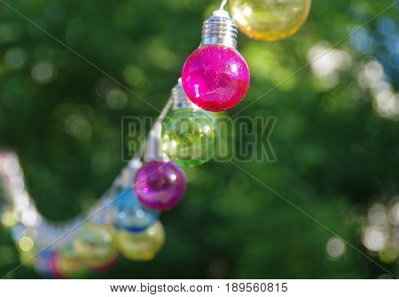 Colorful vitreous bulbs. Electric lamps on wire.