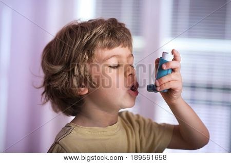Boy using asthma inhaler to treat inflammatory disease wheezing coughing chest tightness and shortness of breath. Allergy treating concept.
