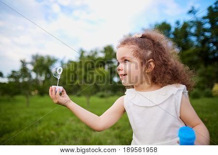 Child is playing with soap bubbles in the park.