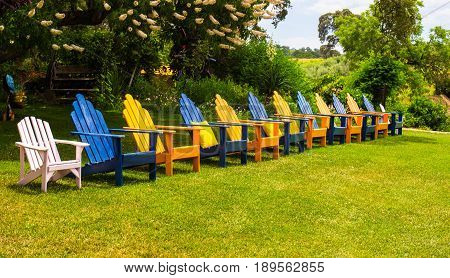 Row of Multi Colored Lawn Chairs With Arm Rests