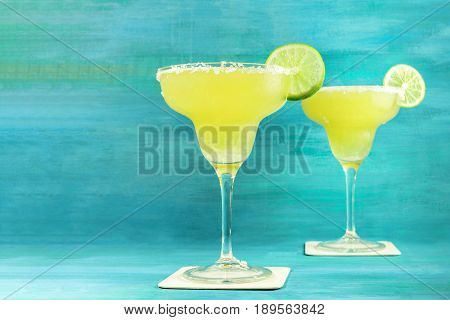 Lemon Margarita cocktails with wedges of lime on a vibrant turquoise background with copy space