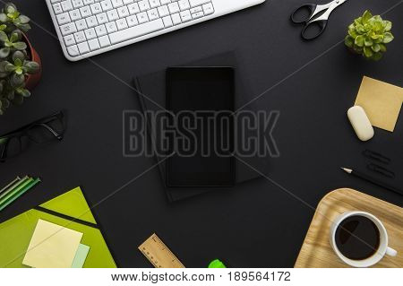 Directly above shot of digital tablet with blank screen surrounded with office supplies on gray desk