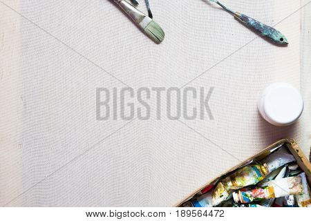 Handmade decore workplace flat lay. Oil paints, brushes, canvas. Artist's equipment assortment background. Drawing lessons, art school, young painter, creativity, DIY concept