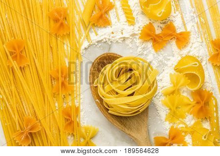 Vibrant pasta texture with spaghetti, bowtie pasta, and pappardelle, on a white marble table with flour