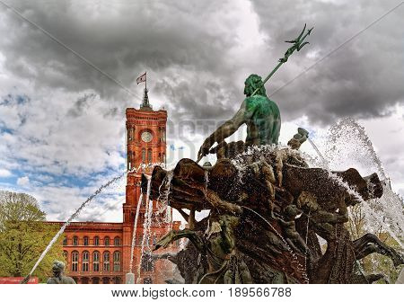 Neptune fountain in Alexanderplatz in Berlin, Germany, with Rotes Rathaus  (Red Town Hall) in the background, before rain.