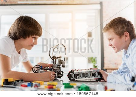 Confident merry boys are looking at each other with smile. They using robots for play