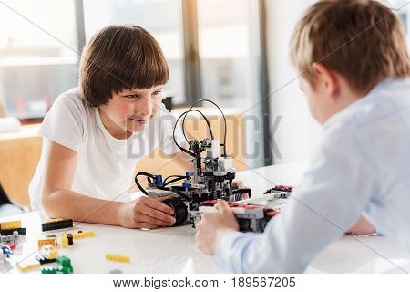 Cheerful male kid is inclining on table and looking at his opponent with sly smile. He holding ready made robot