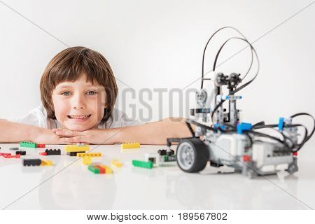 Hilarious boy is putting head on hands and looking at camera with smile. He squatting behind countertop, full of lego spare parts. Portrait