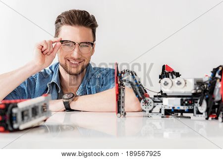 Jolly man is looking at camera with wide smile. Robots are on countertop. Portrait