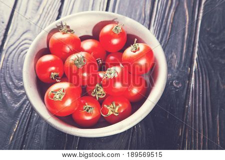 many raw fresh red ripe tomatoes in old dish