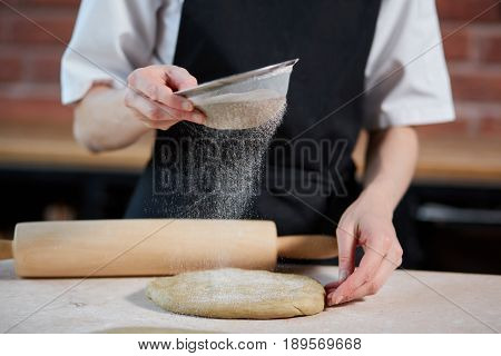 Horizontal indoors crop shot of cook adding flour to the knead on a kitchen of restaurant. Unrecognizable cook making dough. Making dough