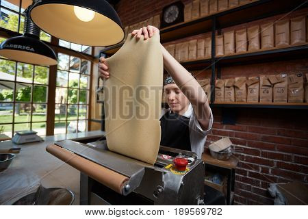 Woman working on kitchen of cafe and rolling a dough through machine. Female cook rolling dough. Making pasta. Making pasta in restaurant.
