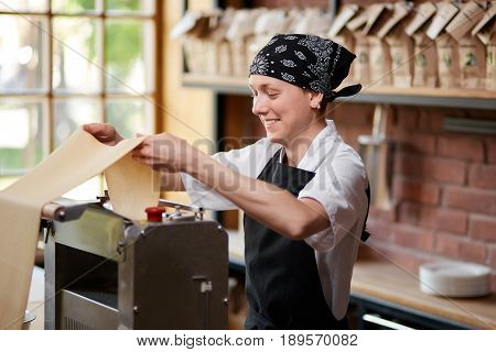 Cheerful female cook rolling pasta knead through machine in cafekithcen. Making pasta. Making pasta in restaurant. Smiling employee cooking pasta in restaurant