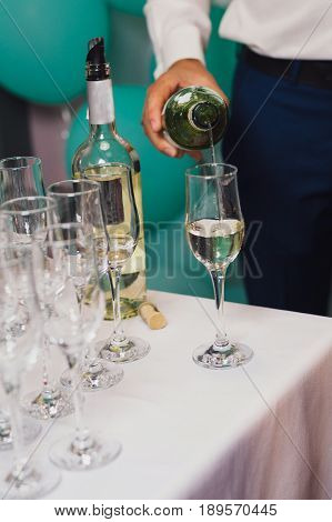 waiter pours wine into the glasses at the buffet table