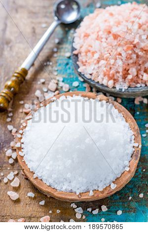 Different types of natural salt in stone bowls on wooden surface. White sea salt pink Himalayan salt