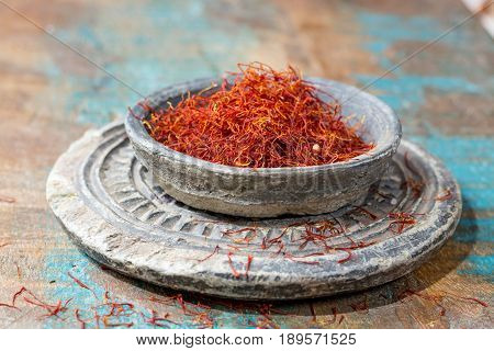 Dried organic red saffron Spice on wooden background with spoon